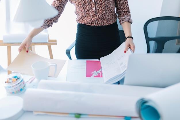 Primer plano de una empresaria sosteniendo un archivo abierto en el escritorio Foto gratis