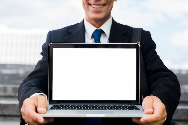Primer plano de un empresario maduro feliz mostrando portátil con pantalla en blanco en blanco Foto gratis