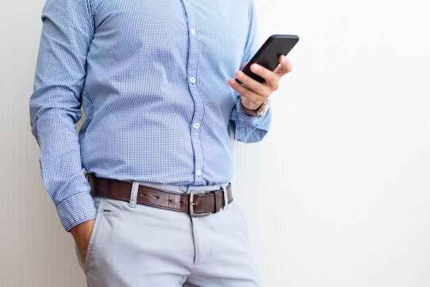 Primer plano de empresario mensajes de texto en el teléfono inteligente Foto gratis