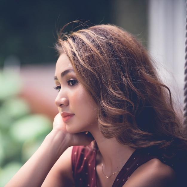 Primer plano de una encantadora mujer asiática soñando con la barbilla descansando en su palma Foto gratis