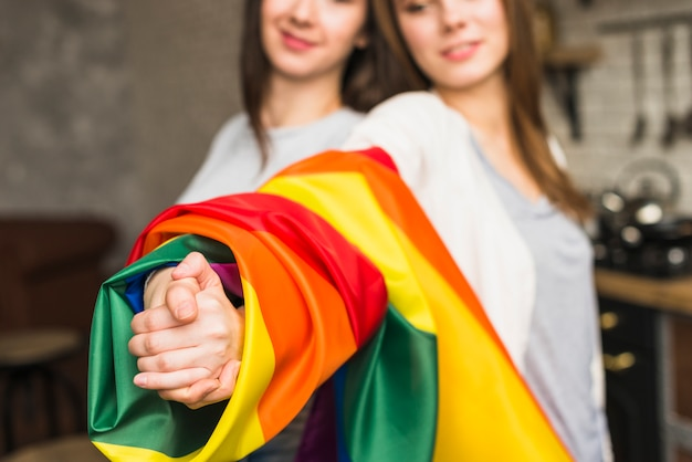Primer plano de una encantadora pareja de jóvenes lesbianas tomándose las manos con la bandera de orgullo envuelto lgbt Foto gratis