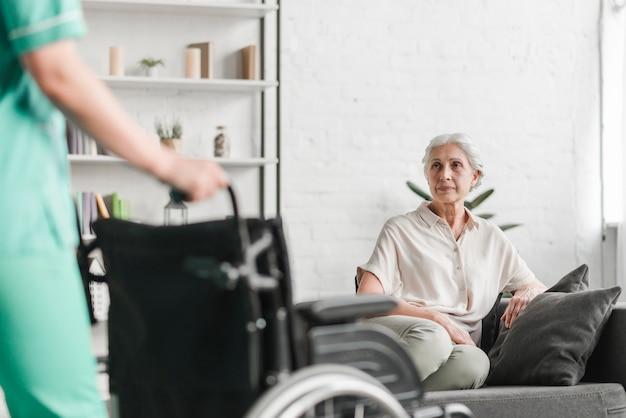 Primer plano, de, enfermera, tenencia, sillón de ruedas, delante de, paciente mayor Foto gratis