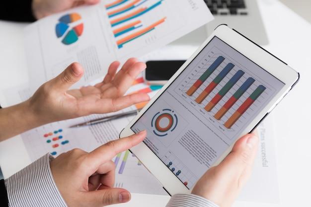 Primer plano de equipo de negocios que usa la tableta digital con d financiera Foto gratis