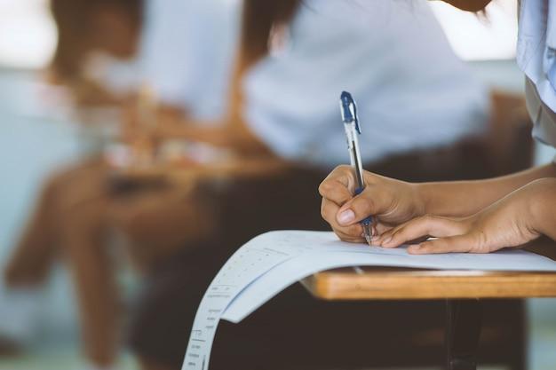Primer plano de escribir las manos de los estudiantes de uniformes para examinar o probar en el aula en la escuela. Foto Premium