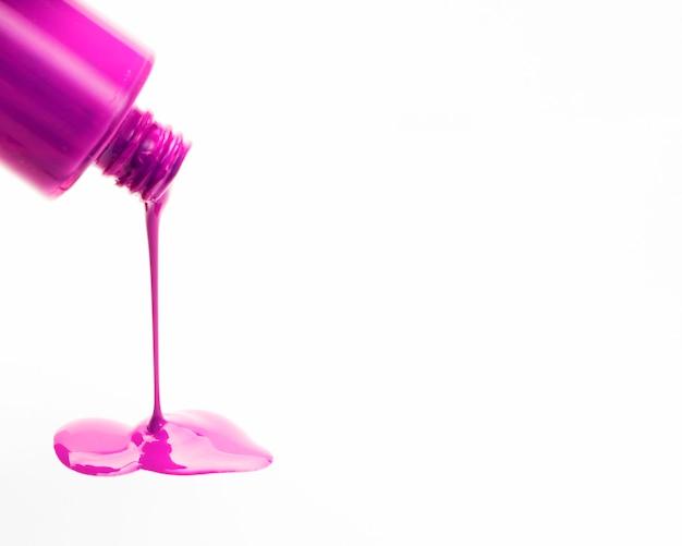 Primer plano de esmalte de uñas rosa derramando fuera de botellas Foto gratis