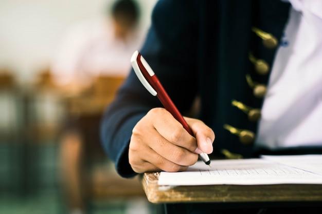 Primer plano estudiantes que escriben y leen las hojas de respuestas del examen ejercicios en el aula de la escuela con estrés. Foto Premium