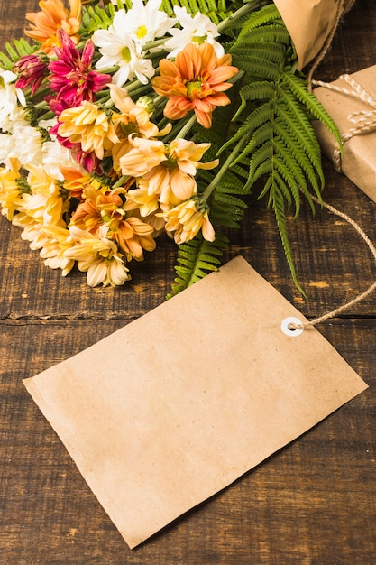 Primer plano de etiqueta en blanco cerca de ramo de flores frescas Foto gratis