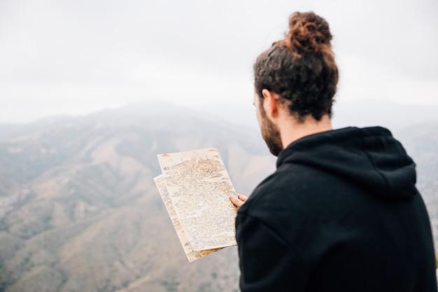 Primer plano de un excursionista masculino leyendo el mapa Foto gratis