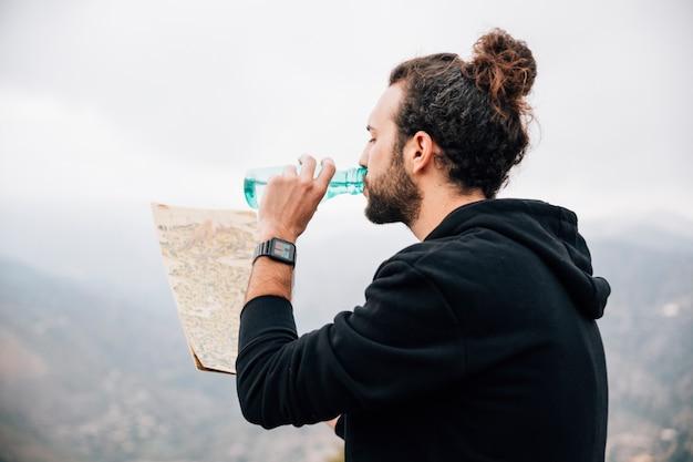Primer plano de un excursionista masculino mirando el mapa bebiendo el agua de la botella Foto gratis