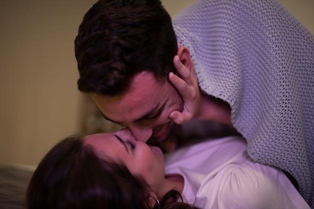 Primer plano feliz joven pareja besándose Foto gratis