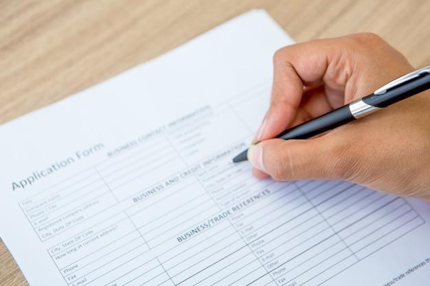 Primer plano de formulario de solicitud llenado mano femenina Foto gratis