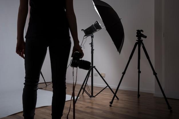 Primer plano de un fotógrafo mujer sosteniendo la cámara en estudio fotográfico Foto gratis