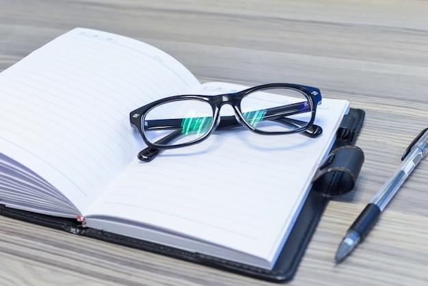 Primer plano de gafas sobre la agenda abierta Foto gratis