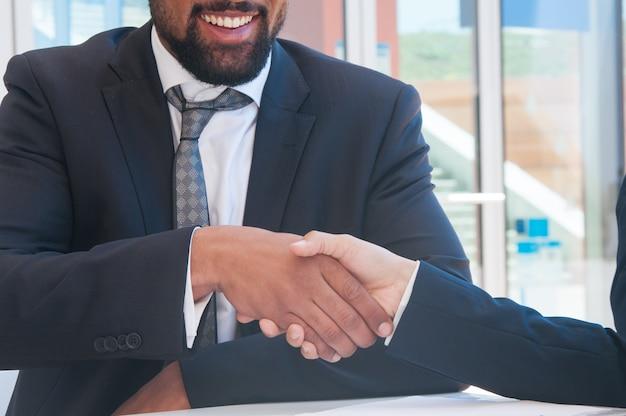 Primer plano de gente de negocios dándose la mano en un café al aire libre Foto gratis