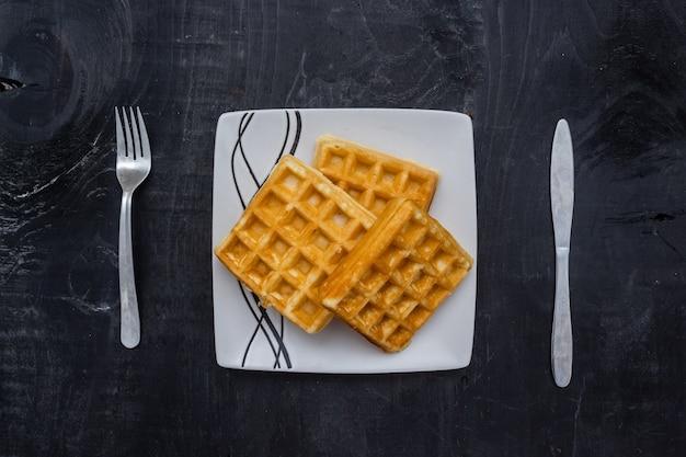 Primer plano de gofres cuadrados sobre una mesa de madera Foto gratis