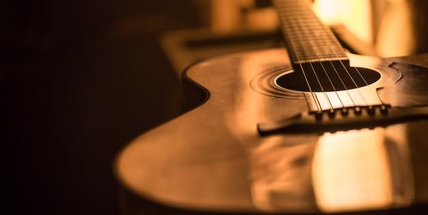 Primer plano de la guitarra acústica en un hermoso fondo de color Foto gratis