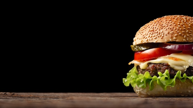 Primer plano de hamburguesa casera con carne de res, tomate, lechuga, queso y cebolla en mesa de madera. Foto Premium