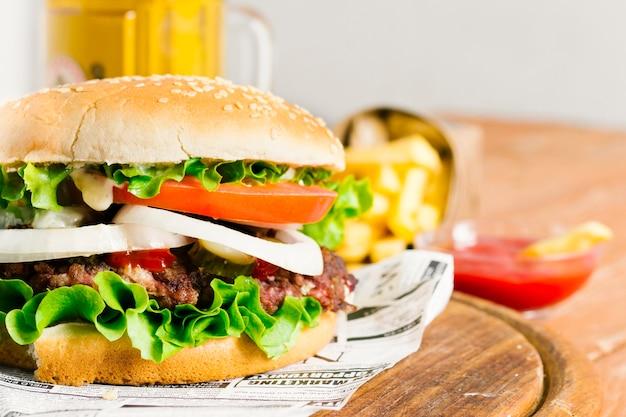 Primer plano de hamburguesa y papas fritas en tablero de madera Foto gratis