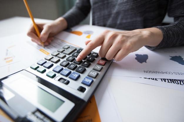 Primer plano, hembra, mano, contando, calculadora Foto gratis