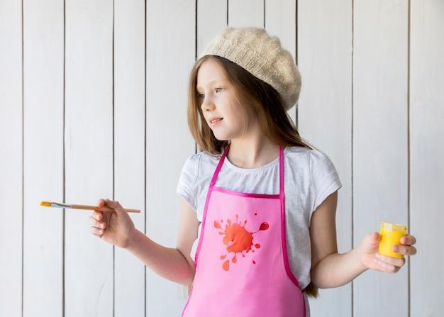 Primer plano de una hermosa niña con pintura amarilla y pincel en la mano de pie contra la pared de madera Foto gratis