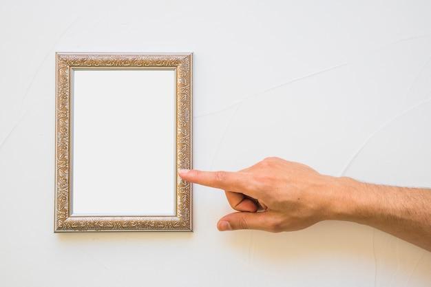 Primer plano de hombre apuntando al marco dorado blanco en pared Foto gratis
