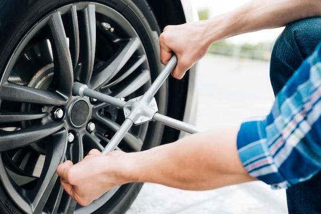 Primer plano del hombre cambiando la rueda del coche Foto gratis