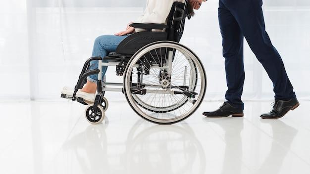 Primer plano de un hombre empujando a la mujer sentada en silla de ruedas Foto gratis