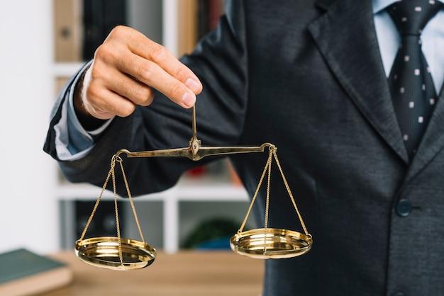 Primer plano de hombre con escalas de oro de la justicia en la mano Foto gratis