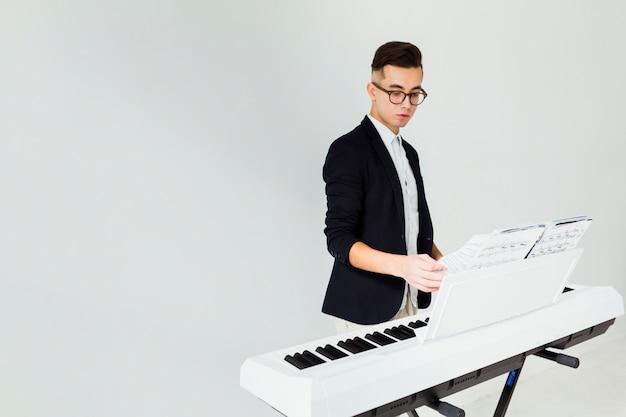 Primer plano de un hombre joven que da vuelta a las páginas de la hoja musical en el piano aislado en el fondo blanco Foto gratis