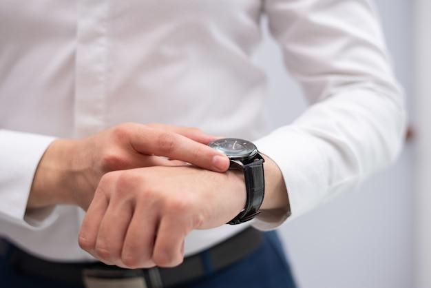 Primer plano de hombre de negocios mirando su reloj de pulsera ... a7360c7155f6