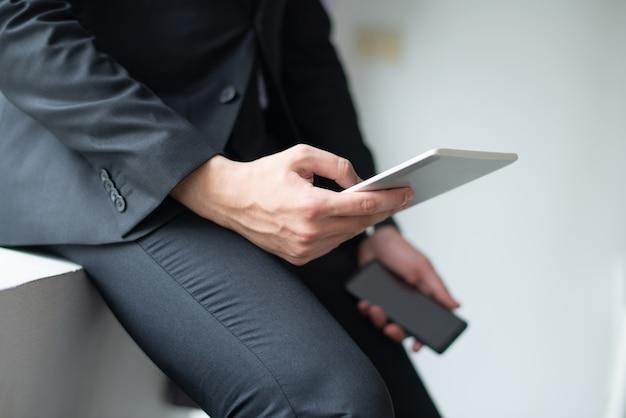 Primer plano de hombre de negocios usando gadgets y apoyándose en el alféizar Foto gratis
