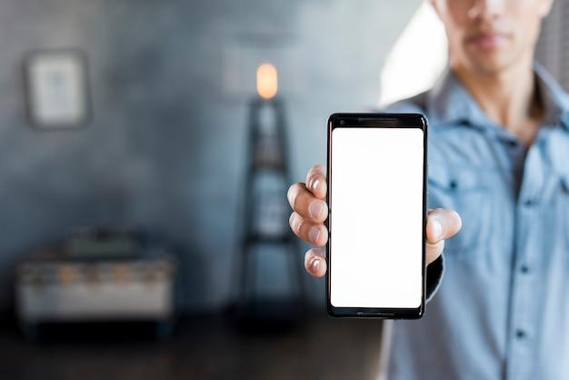 Primer plano de un hombre que muestra un teléfono inteligente con pantalla blanca en la mano Foto gratis