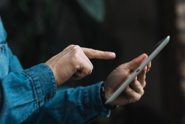 Primer plano del hombre que señala el dedo sobre la tableta digital Foto gratis