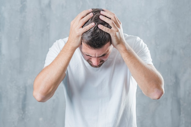 Close-up of a man suffering from a headache against a gray background