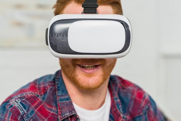 Primer plano de un hombre sonriente con gafas de realidad virtual Foto gratis