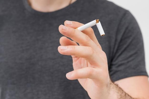 Primer plano del hombre sosteniendo el cigarrillo roto en sus dos dedos Foto gratis