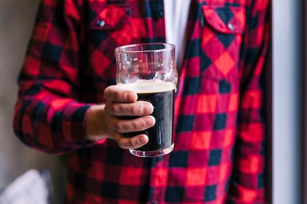 Primer plano, de, hombre, tenencia, cerveza, vidrio, en, mano Foto gratis