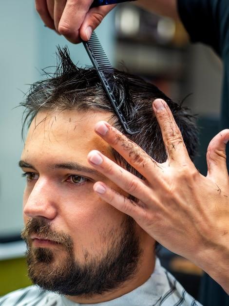 Primer plano del hombre de la vista lateral que consigue corte de pelo profesional Foto gratis