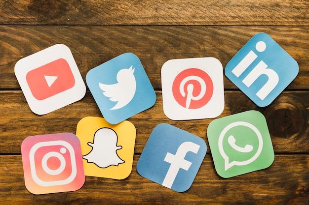 Primer plano de los iconos de redes sociales en la mesa de madera Foto gratis