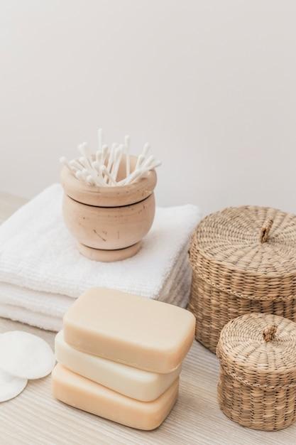 Primer plano de jabones; esponja; bastoncillo de algodón; toalla y cesta de mimbre en superficie de madera. Foto gratis