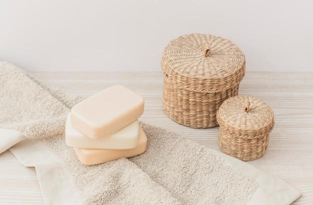 Primer plano de jabones; toalla y cesta de mimbre en superficie de madera. Foto gratis