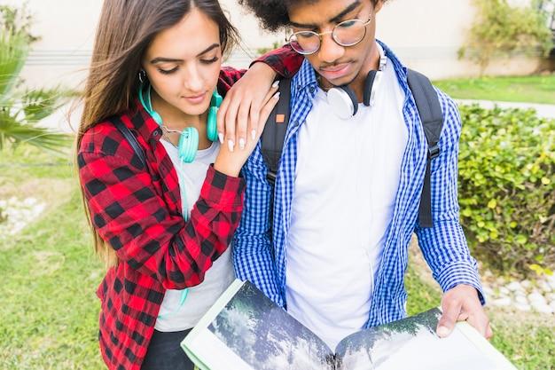 Primer plano de un joven estudiante masculino y femenino leyendo los libros en el parque Foto gratis
