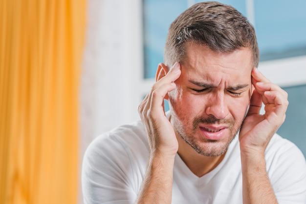 Primer plano de un joven haciendo muecas de dolor al tocar su cabeza con los dedos Foto gratis