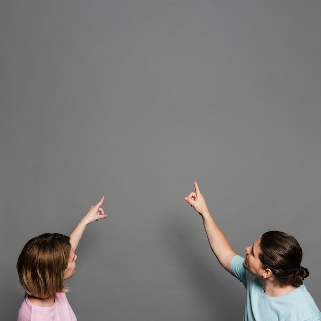 Primer plano de la joven pareja apuntando sus dedos hacia arriba contra la pared gris Foto gratis