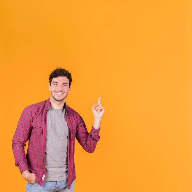 Primer plano de un joven sonriente apuntando su dedo hacia arriba contra un fondo naranja Foto gratis