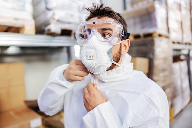 Primer plano de un joven trabajador en uniforme estéril y máscara protectora y gafas de pie en el almacén y uniforme con cremallera. se prepara para esterilizar el almacén. concepto de brote de corona. Foto Premium