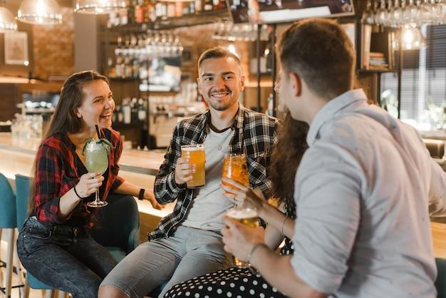 Primer plano de jóvenes amigos disfrutando de bebidas por la noche en la discoteca Foto gratis