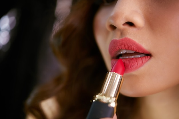 Primer plano de lápiz labial tocando los labios femeninos rojos regordetes Foto gratis