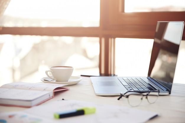 Primer plano lateral de un escritorio de trabajo con la computadora portátil, una taza de café, anteojos y artículos de papelería Foto gratis