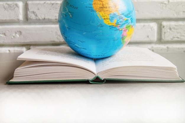 Primer plano de un libro abierto sobre una biblioteca libros de mesa y un globo terráqueo, contra una pared de ladrillos en el aula, la luz solar, el concepto del día mundial del libro Foto Premium
